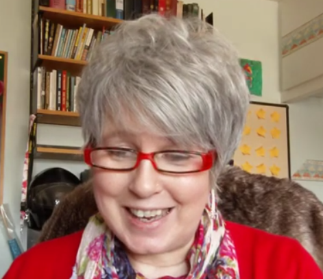 A photo of Kay wearing red glasses, a red cardigan and a flowery scarf with red flowers