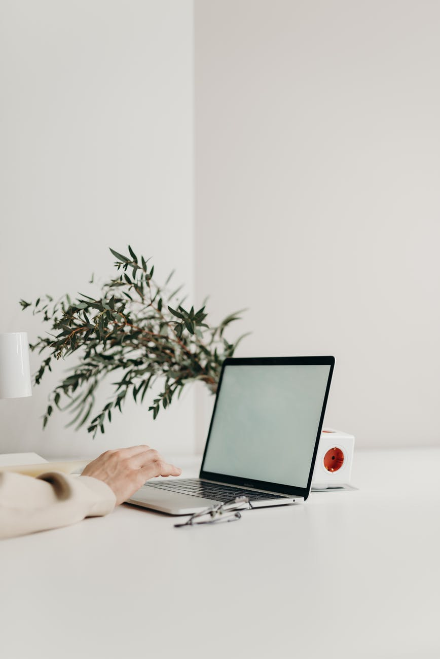 person using black laptop computer on white table, glasses folded in front of the computer, and a foliage plant behind it.