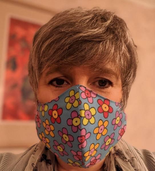 Photo of Kay wearing a flowery light blue mask