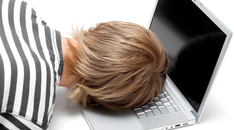 A man in a striped top sleeping with his head on his laptop. You can only see the back of his head.