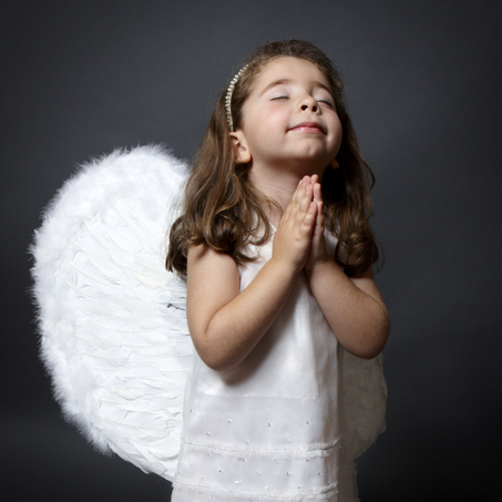 Little barefoot angel in white dress and feathered wings with hands together in quiet prayer