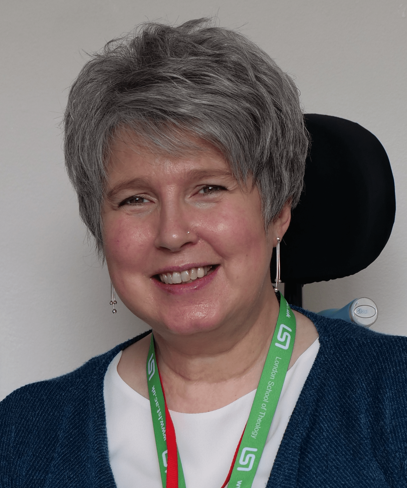 Photo of Kay. Head and shoulders shot, with wheelchair slightly visibles